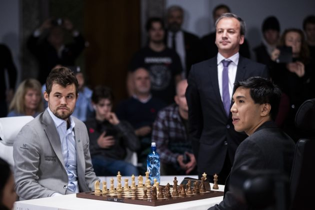 Šahisti Magnus Karlsen i Vesli So poziraju za šahovskom tablom pred početak meča