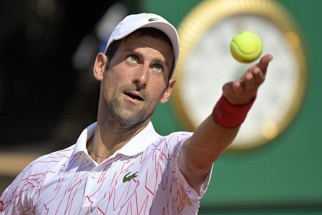 Novak Đoković gleda u lopticu dok izvodi servis