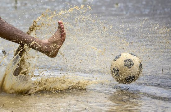 Dečak šutira loptu u vodi